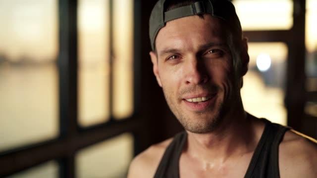 ritratto di uomo sorridente in palestra - abbigliamento sportivo video stock e b–roll