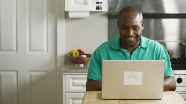 ms portrait of smiling man using laptop in kitchen / edmonds, washington, usa - 正面から見た図点の映像素材/bロール