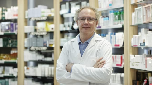 portrait of smiling mature chemist at pharmacy - pharmacist stock videos & royalty-free footage