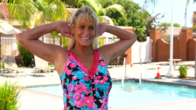 vidéos et rushes de ms portrait of smiling mature female synchronized swimmer on pool deck - maillot de bain