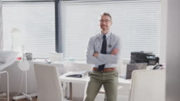 Portrait Of Smiling Mature Male Doctor Sitting On Desk In Office