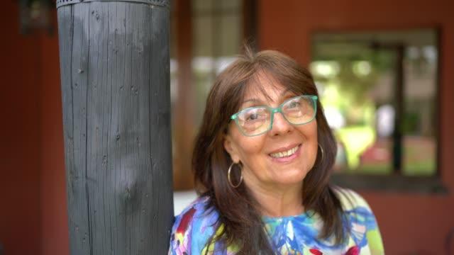vídeos y material grabado en eventos de stock de retrato de mujer madura sonriente en casa - 55 59 años