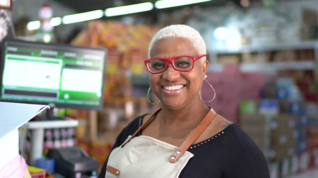 portrait of smiling mature woman cashier at wholesale - occhiali da vista video stock e b–roll