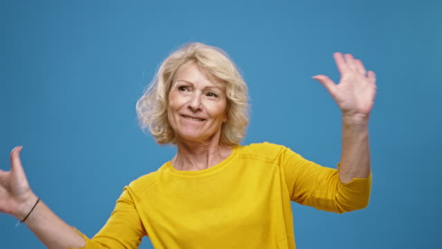 portrait of smiling mature woman having fun against a blue background - coloured background stock videos & royalty-free footage