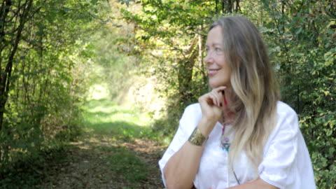 stockvideo's en b-roll-footage met portret van glimlachen rijpe vrouw in de natuur - hippie