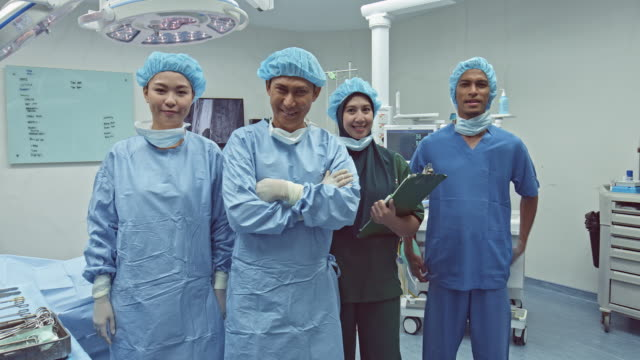 portrait of smiling medical team in the operating room - surgeon stock videos & royalty-free footage