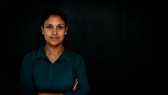 portrait of smiling mid adult businesswoman standing arms crossed over gray background - gray background stock videos and b-roll footage