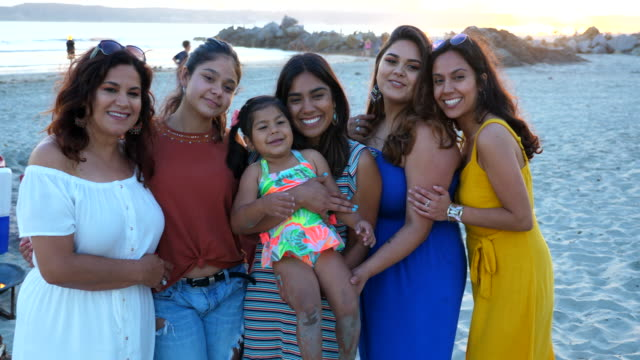 vídeos de stock e filmes b-roll de ms portrait of smiling mother adult daughters and granddaughter on beach during family party - 25 29 anos