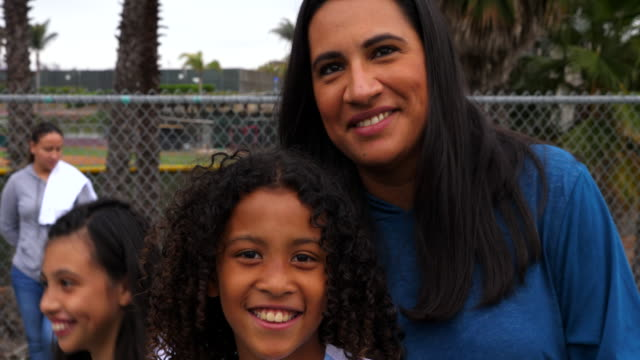 ms portrait of smiling mother and daughter embracing on sidelines after soccer game - pacific islander family stock videos & royalty-free footage