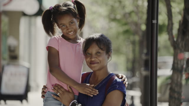 portrait of smiling mother and daughter posing in city / provo, utah, united states - provo stock-videos und b-roll-filmmaterial