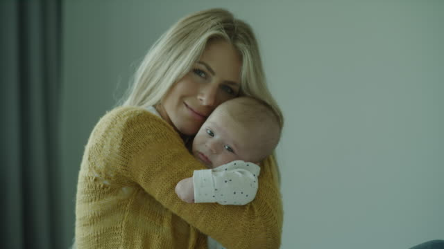 portrait of smiling mother looking at camera and hugging baby son / lehi, utah, united states - lehi stock videos & royalty-free footage