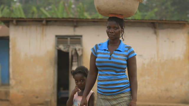 Portrait of smiling mother while carrying water on her head