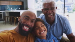 Portrait Of Smiling Multi-Generation Male African American Family Sitting On Sofa At Home
