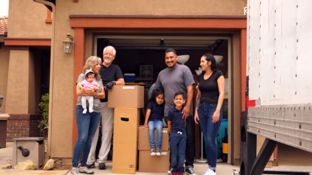 ms portrait of smiling multigenerational family standing in front of new home on moving day - baby girls stock videos & royalty-free footage