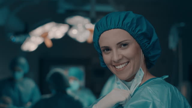 portrait of smiling nurse taking off surgical mask - surgeon stock videos & royalty-free footage