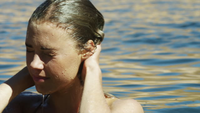 vídeos de stock e filmes b-roll de cu portrait of smiling of young woman emerging from lake powell / utah, usa - cabelo molhado