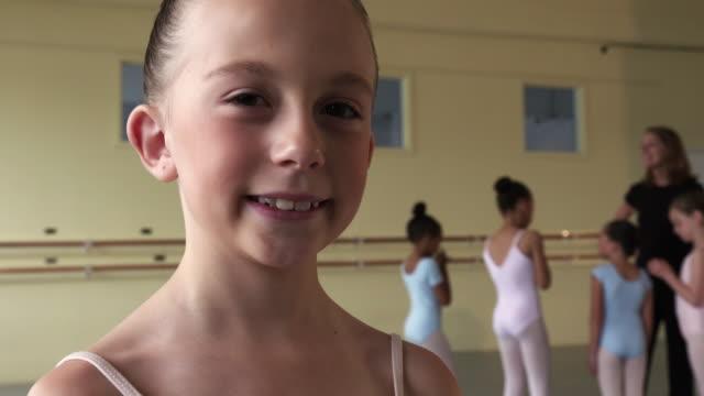 vídeos de stock, filmes e b-roll de portrait of smiling preteen ballerina with people in background - cabelo preso