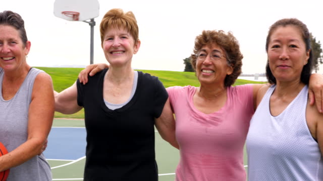 pan portrait of smiling senior and mature women standing on outdoor basketball court after game - 50 54 years stock videos & royalty-free footage