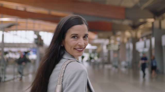 slo mo. portrait of smiling senior businesswoman walking through lively airport terminal. - geschäftsreise stock-videos und b-roll-filmmaterial
