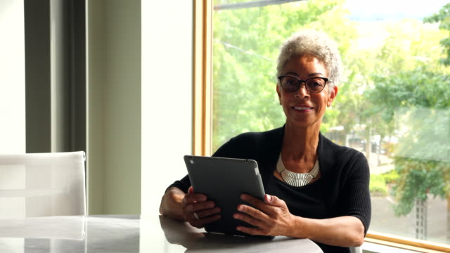 ms portrait of smiling senior businesswoman working on digital tablet in office conference room - working seniors stock videos & royalty-free footage