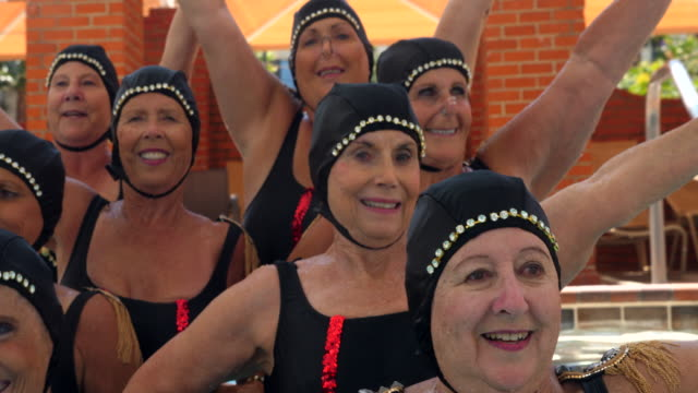 pan portrait of smiling senior female synchronized swim team on steps of pool - swimming costume stock videos & royalty-free footage