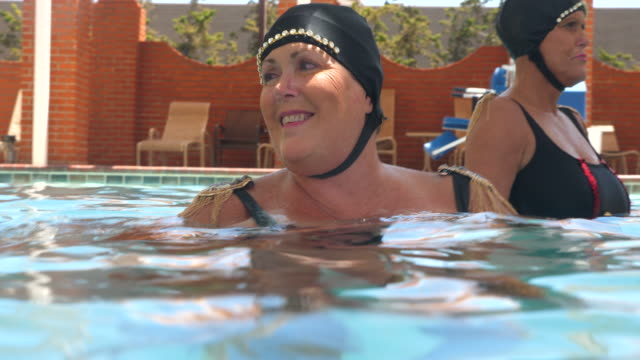 ms portrait of smiling senior female synchronized swimmers standing in pool after practicing routine - caucasian appearance stock videos & royalty-free footage
