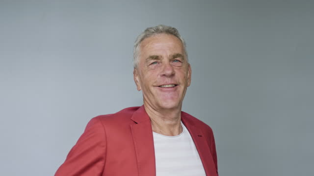 porträt von smiling senior male in red blazer - one senior man only stock-videos und b-roll-filmmaterial