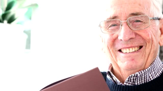 Portrait Of Smiling Senior Man Reading Book At Home