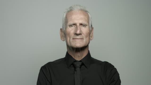 vídeos y material grabado en eventos de stock de portrait of smiling senior man - fondo gris