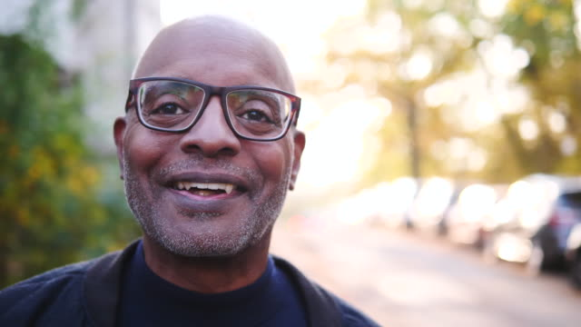 stockvideo's en b-roll-footage met portrait of smiling senior man wearing eyeglasses on street - shaky