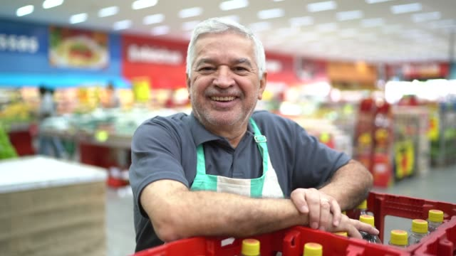 vídeos de stock e filmes b-roll de portrait of smiling senior supermarket employee - employee