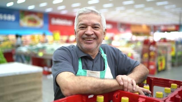 vidéos et rushes de verticale d'employé aîné de supermarché de sourire - vendeur