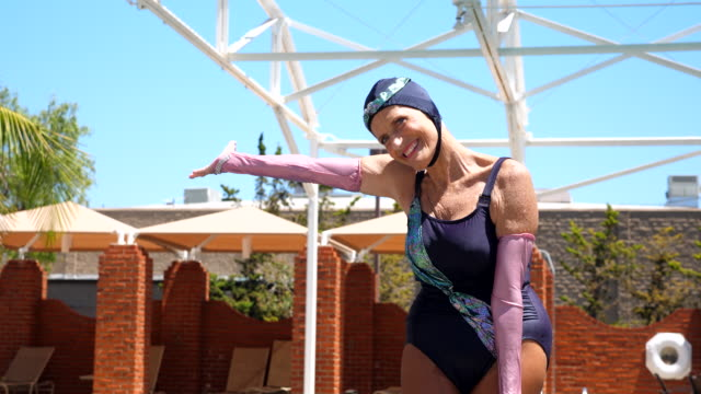 ms portrait of smiling senior synchronized swimmer exiting pool after routine - caucasian appearance stock videos & royalty-free footage