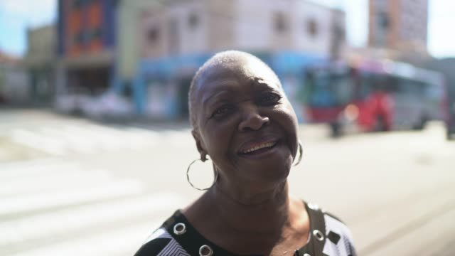portrait of smiling senior woman at city street - completely bald stock videos & royalty-free footage