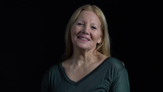 porträt der lächelnde ältere frau mit blonden haaren - schwarzer hintergrund stock-videos und b-roll-filmmaterial