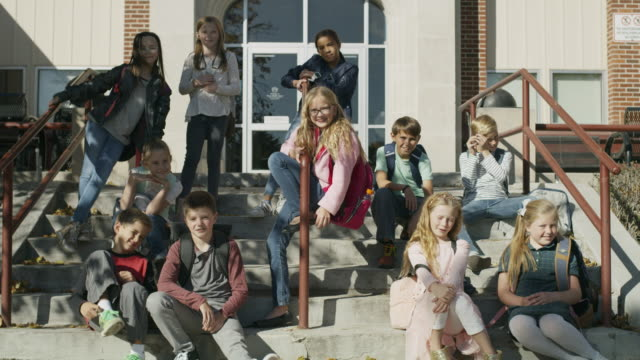 Portrait of smiling students sitting on staircase at school / Provo, Utah, United States
