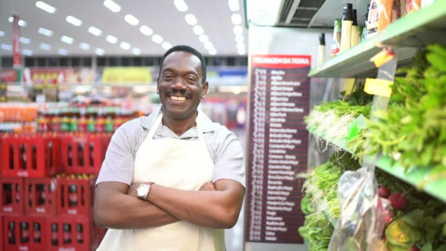 stockvideo's en b-roll-footage met portret van lachende supermarkt werknemer kijken naar camera - straatverkoper