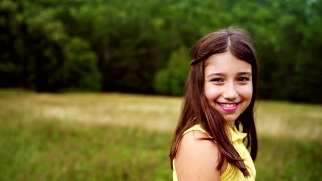 vídeos de stock e filmes b-roll de portrait of smiling teenage girl on a meadow - 10 11 anos