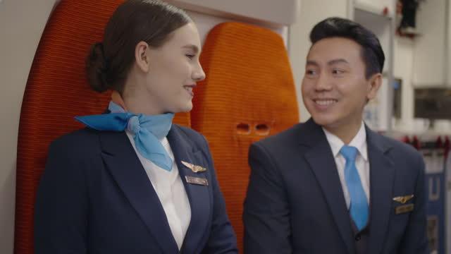vídeos de stock e filmes b-roll de portrait of smiling two cabin crew talking together during flight - fazer uma pausa