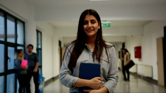 portrait of smiling university student standing in corridor during break - part of a series stock videos & royalty-free footage