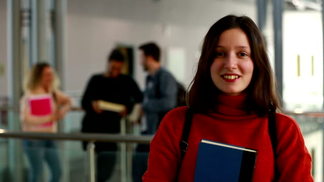 portrait of smiling university student standing in corridor during break - female high school student stock videos & royalty-free footage