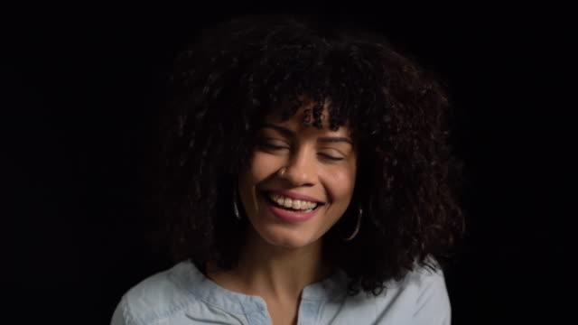 vídeos de stock, filmes e b-roll de retrato de uma mulher sorridente contra fundo preto - fundo preto