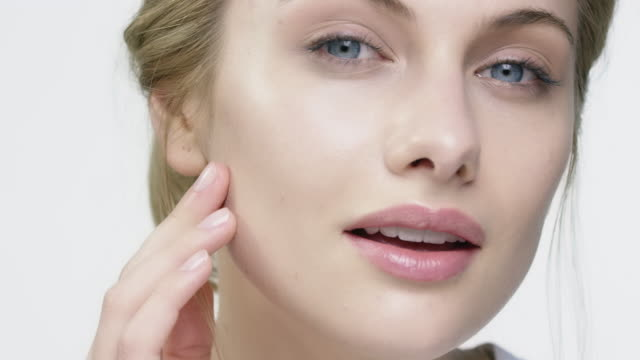 portrait of smiling woman applying face cream - beauty treatment stock videos and b-roll footage