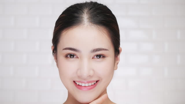 portrait of smiling woman applying face cream. - beautiful woman stock videos & royalty-free footage