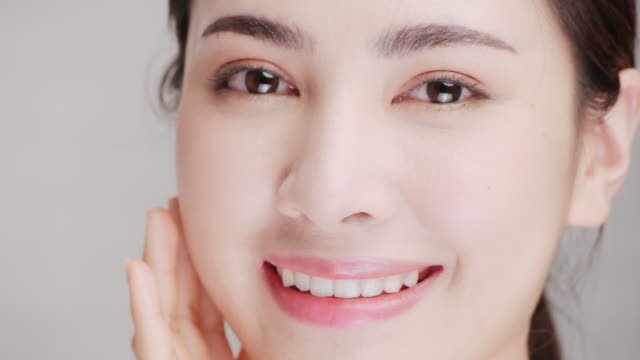 slo mo, portrait of smiling woman applying face cream. - one young woman only stock videos & royalty-free footage