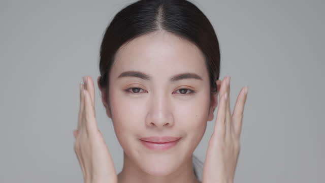 portrait of smiling woman applying face cream. - applying stock videos & royalty-free footage