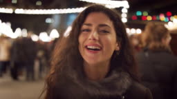 Portrait Of Smiling Woman Enjoying Christmas Market At Night