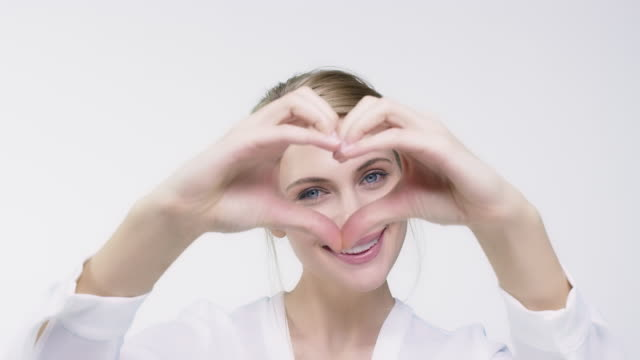 portrait of smiling woman making heart shape - pouting stock videos & royalty-free footage