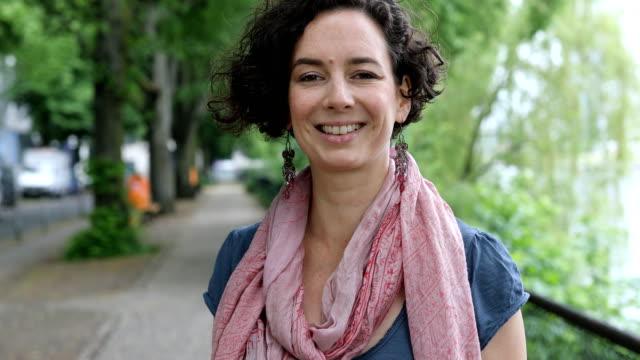 Portrait of smiling woman on sidewalk in city
