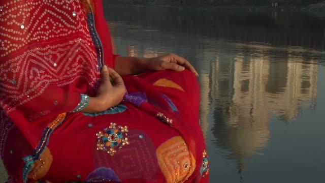 cu, tu, portrait of smiling woman sitting by water, taj mahal in background, agra, uttar pradesh, india - agra stock videos and b-roll footage